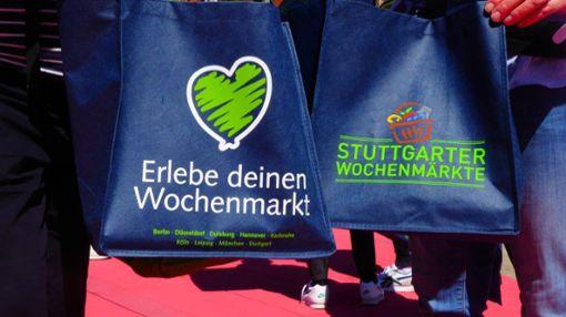 Mit ihren Taschen machen Kunden schon am Eröffnungs-Tag Werbung für den Wochenmarkt auf dem  Marienplatz in der Landeshauptstadt.    Foto: Katrin Schenk