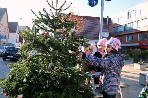 Kindergartenkinder schmücken Weihnachtsbäume auf dem Zeppelinplatz in Echterdingen.  Foto: Eva Herschmann
