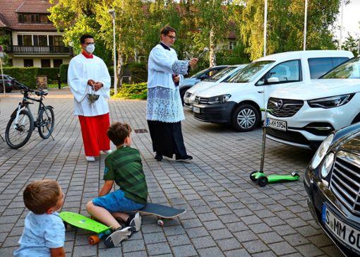 Diakon Jakob besprengt alle Fahrzeuge vor dem Gotteshaus mit Weihwasser, Roller und Skateboards inklusive.  Foto: Eva Herschmann
